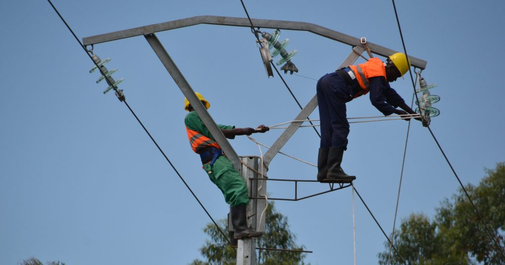 Two men work on some power lines