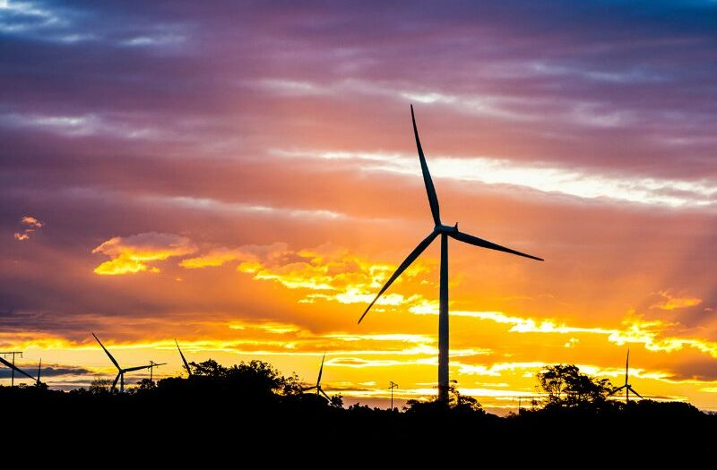 Wind turbine against a sunset sky