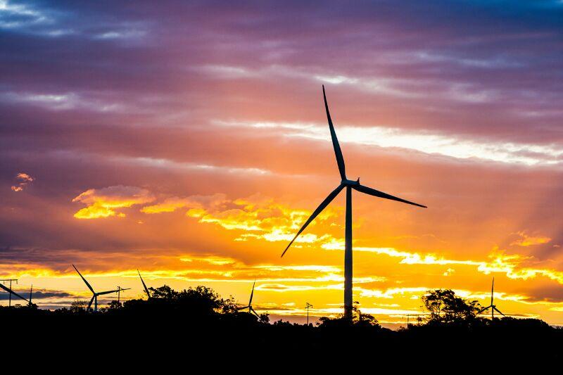 Wind turbine against a sunset sky