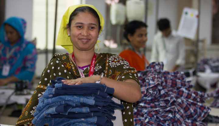 Woman carries a pile of jeans demonstrating the supply chain