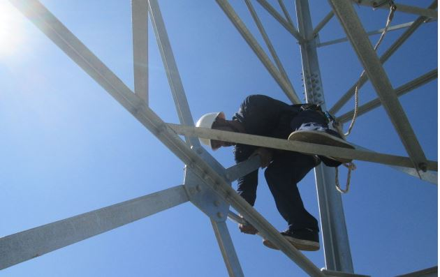 Worker climbs scaffolding to fix something