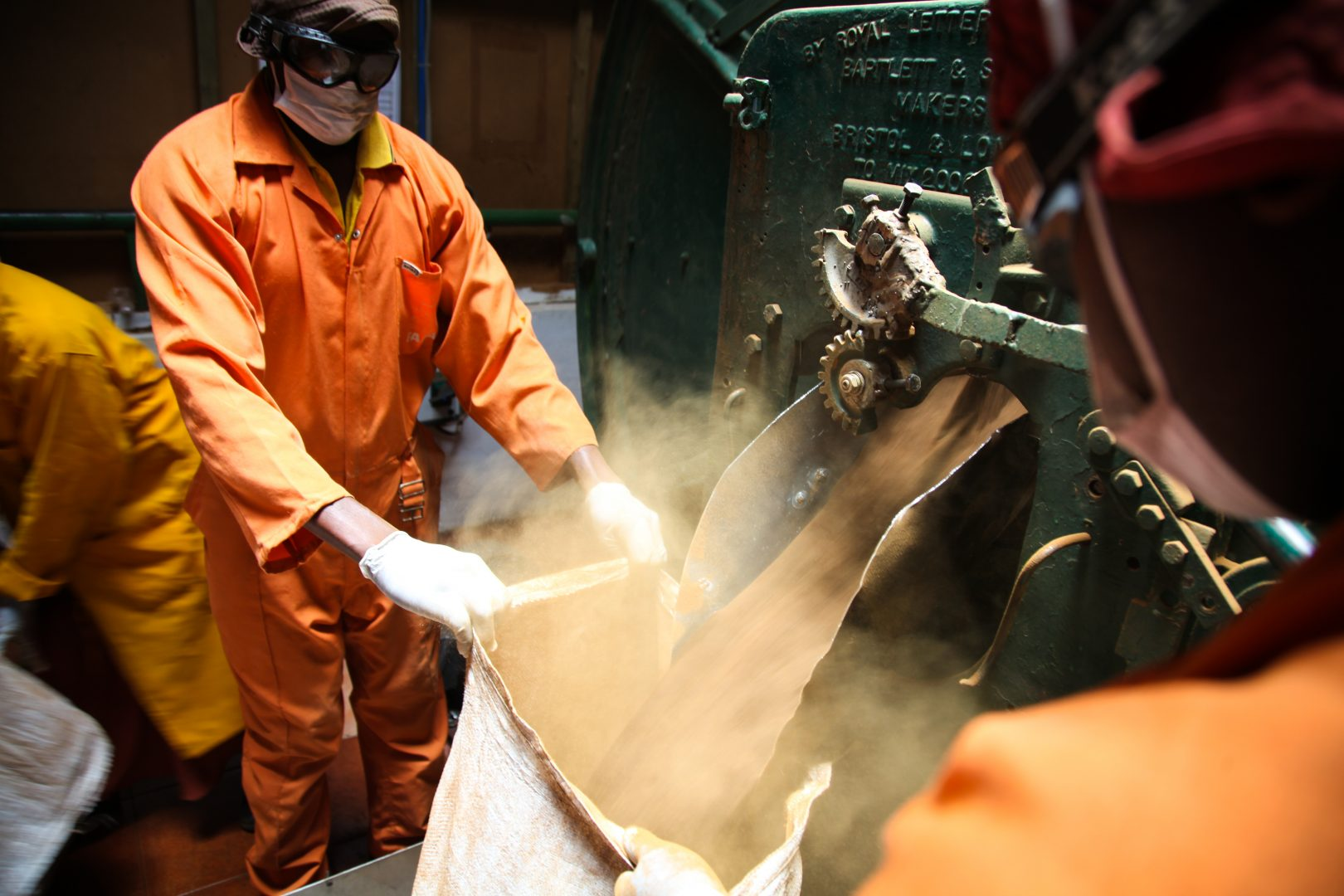 Worker fills sack with dust from a machine