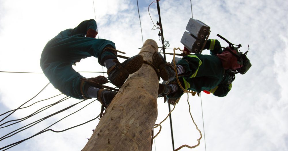 Workers climb a telephone pole to fix something