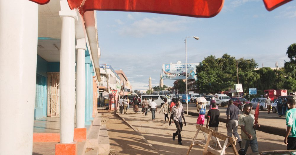 The edges of a red canopy wave in the breeze on a busy street in Lilongwe, Malawi.