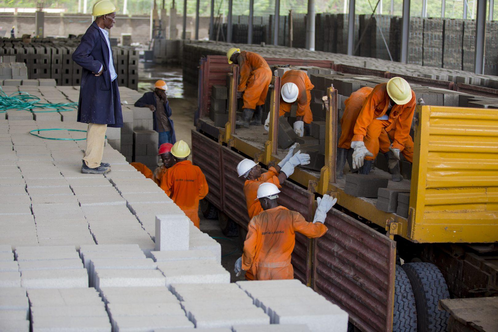 Men unloading cinder blocks from a truck.