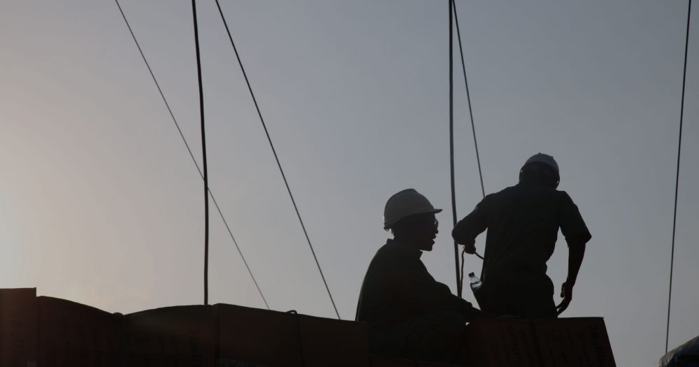 Two silhouettes of men against the sky