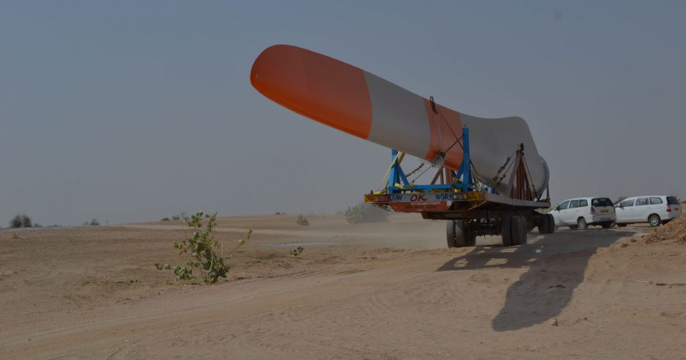 A wind turbine blade gets transported on the back of a trailer