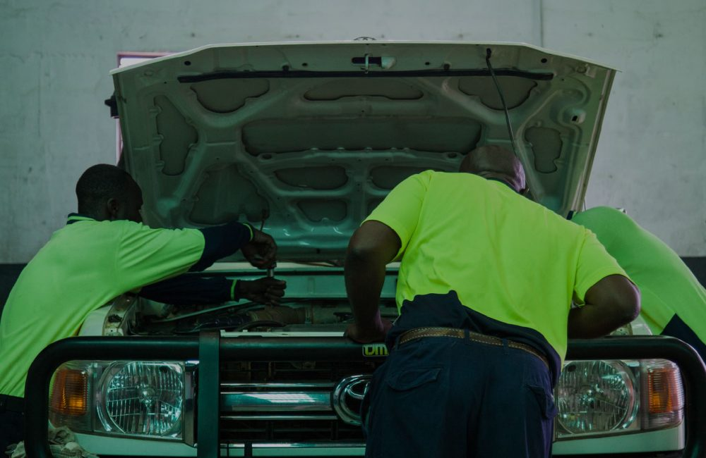 Men in green examine a car engine