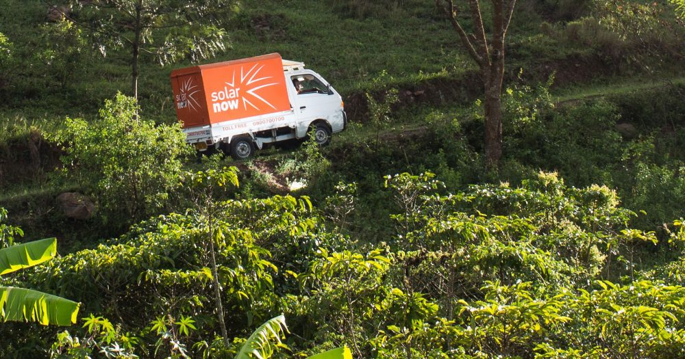 An orange truck drives through a green forest opening