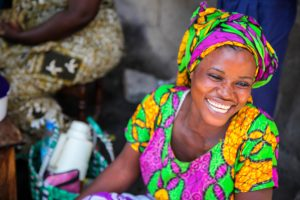A brightly dressed women smiles