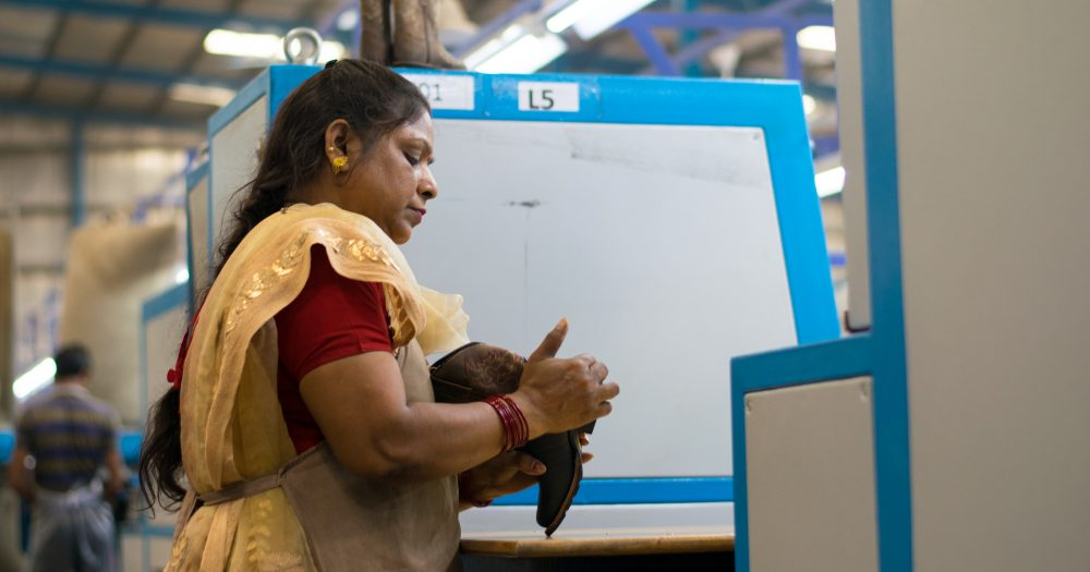 A woman carries out a task for her job in front of a large white box