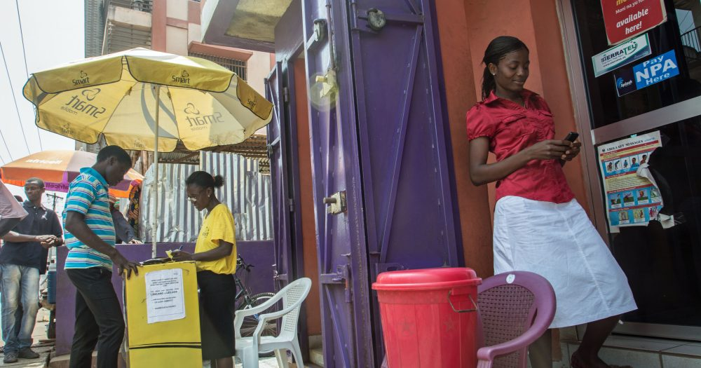 Woman stands outside a brightly coloured shop
