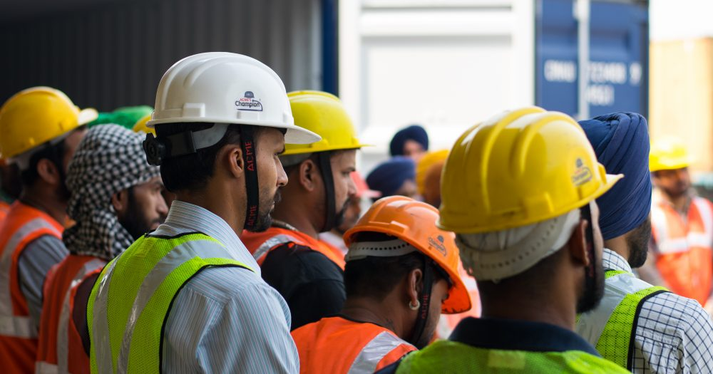 Men gathered around all wearing hard hats