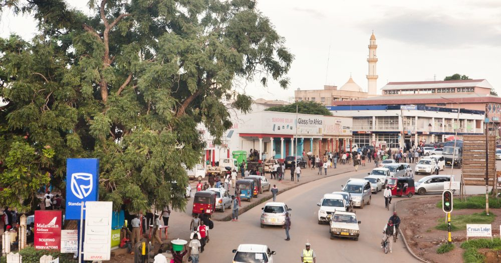 Busy street scene in Malawi with a mosque in the distance