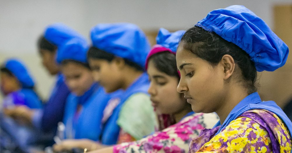 Female factory workers sorting through piles of jeans in Bangladesh