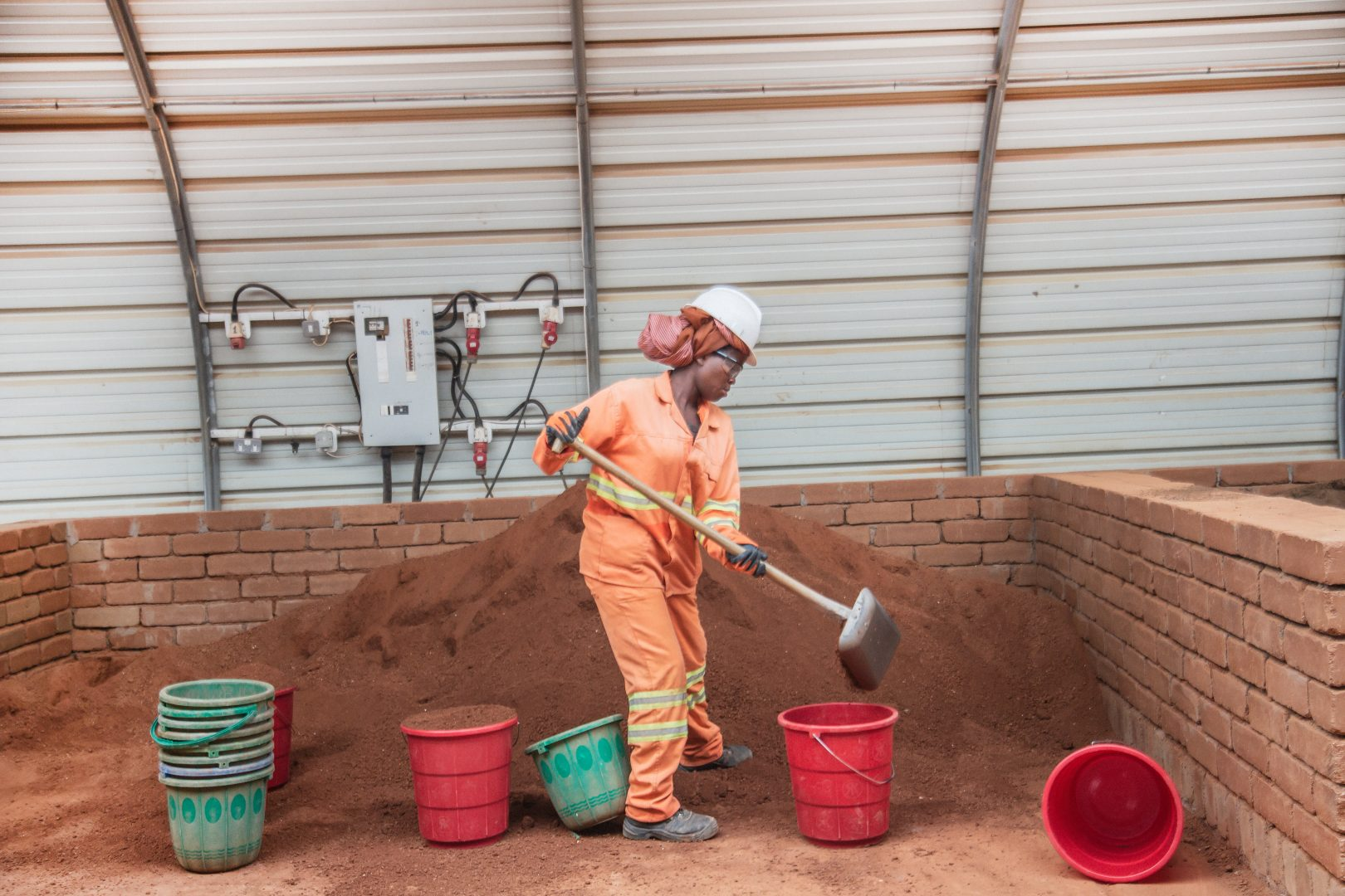 Female worker shovels earth into buckets for brick production