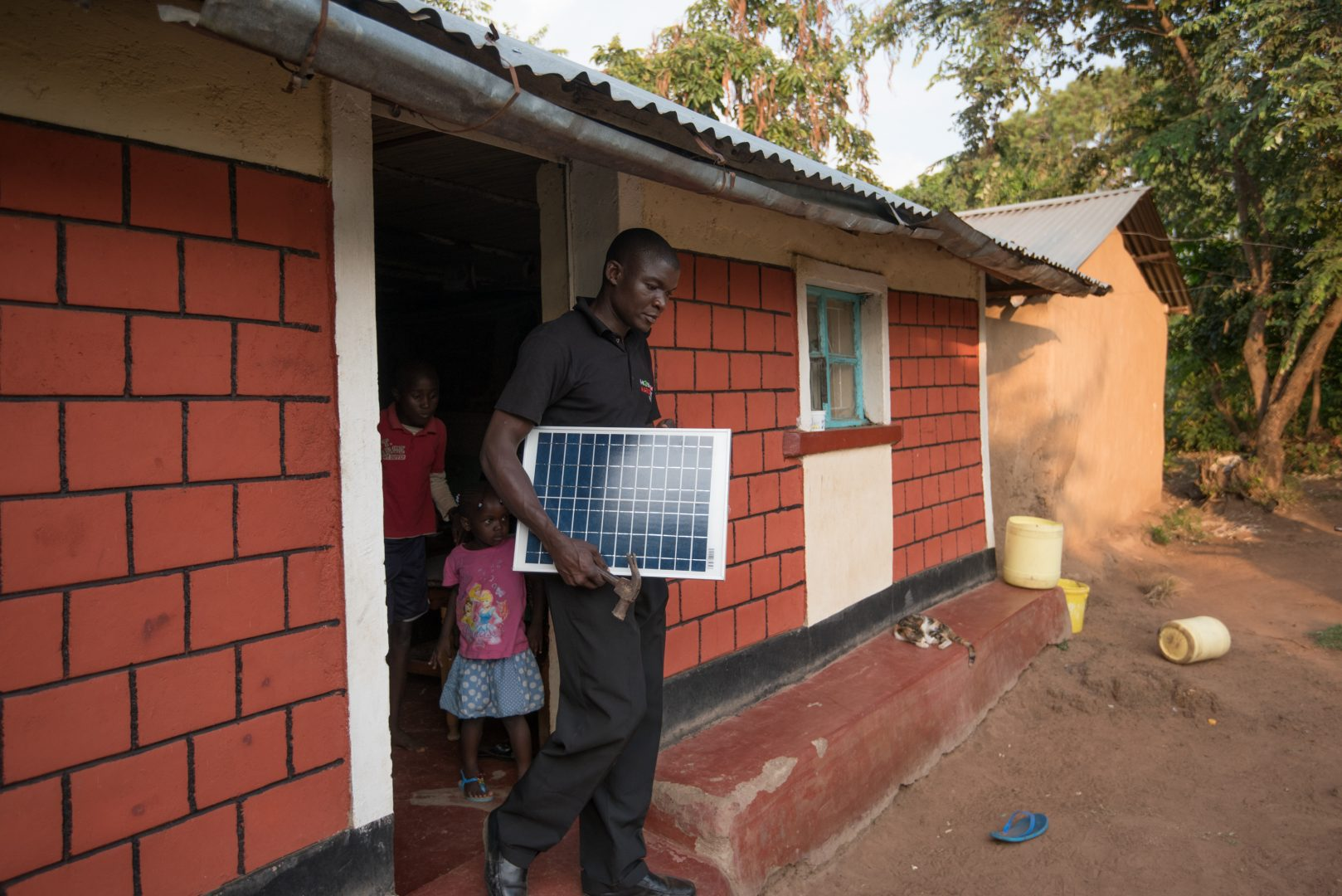 Man carries a solar panel out of a red brick building